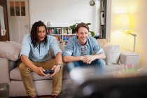 Men playing video games in living room — Stock Photo