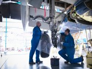 Aircraft engineers working on undercarriage area and landing gear of 737 jet plane — Stock Photo