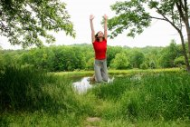 Woman jumping by rural lake — Stock Photo