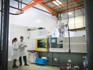 Scientifiques hommes et femmes à côté de la machine de moulage en plastique tenant des notes — Photo de stock