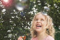 Young girl blowing bubbles, outdoors — Stock Photo