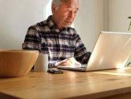 Older man using laptop at table — Stock Photo