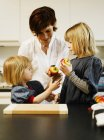 Mother and daughters eating in kitchen — Stock Photo
