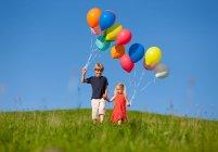 Дети с красочными шарами в траве — стоковое фото