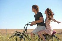 Coppia bicicletta in sella all'erba alta — Foto stock