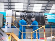 Aircraft engineers working on 737 jet engine in airport — Stock Photo