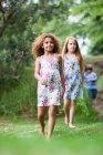 Ragazze che camminano in erba insieme, ragazzo in background — Foto stock