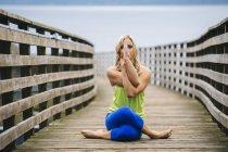 Портрет молодої жінки йоги позувати на дерев'яний причал — стокове фото