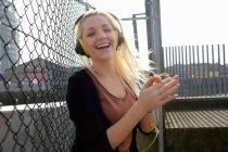 Mujer sonriente escuchando auriculares - foto de stock