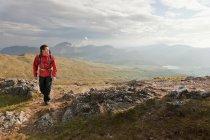 Caminhante andando no topo da montanha rochoso — Fotografia de Stock