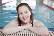 Femme souriante dans la piscine intérieure — Photo de stock