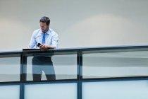 Businessman working on balcony using smartphone — Stock Photo