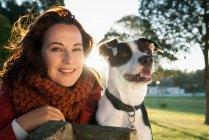 Femme assise avec chien sur banc de parc — Photo de stock