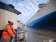 Tug travailleur portant un casque dur regardant le navire — Photo de stock