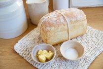 Laib Brot mit Butter und Salz in Schüsseln — Stockfoto