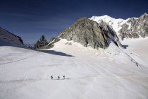 Three hikers walking in winter mountains — Stock Photo