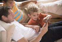 Man and two sons pointing at digital tablet on sofa — стокове фото