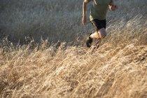 Man running on long grass — Stockfoto