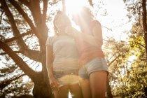 Visão de baixo ângulo de mãe e filha desfrutando da natureza na floresta — Fotografia de Stock