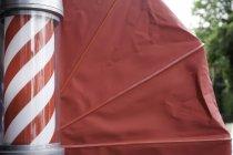Vista lateral do polo de barbeiros e toldo vermelho — Fotografia de Stock