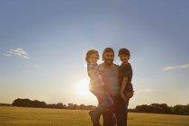 Отец выносил сыновей в солнечный парк — стоковое фото