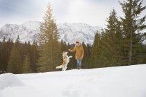 Mujer jugando con husky en paisaje cubierto de nieve, Elmau, Baviera, Alemania - foto de stock