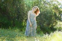 Девушка-подросток, стоящая в поле цветов — стоковое фото