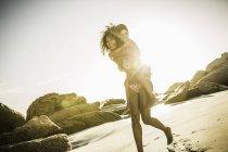Мати даючи син piggyback їздити на пляжі — стокове фото