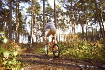 Twin brothers racing BMX bikes in muddy forest — Stock Photo