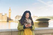 Giovane donna davanti al ponte di Westminster e il Big Ben che osserva giù utilizzando smartphone, Tamigi, Londra, Regno Unito — Foto stock