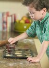 Boy spooning batter into pan in kitchen — Stock Photo