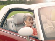 Senior woman driving red convertible — Stock Photo