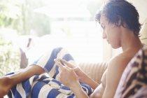 Junger Mann in Smartphone Texte auf patiostuhl Handtuch gewickelt — Stockfoto