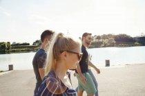 Four young friends walking along riverside — Stock Photo
