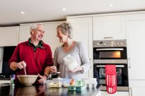 Senior couple baking together in kitchen — Stock Photo