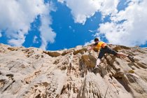 Female rock climber nearing cliff top — Stock Photo