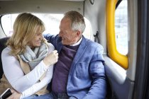 Mature dating couple en route in black cab backseat — Stock Photo