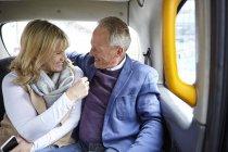 Reifes dating paar unterwegs im schwarzen Taxi Rücksitz — Stockfoto