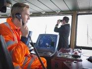 Operaio navale che utilizza telefono e capitano sul ponte della nave — Foto stock