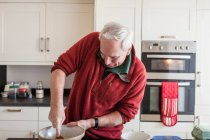 Senior man using wooden spoon in mixing bowl — Stock Photo