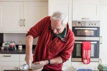 Senior benutzt Kochlöffel in Rührschüssel — Stockfoto