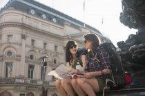 Женщины-туристы, сидящие с картой на ступеньках статуи, Цирк Пиккадили, Лондон, Великобритания — стоковое фото