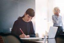 Mature femme d'affaires avec ordinateur portable et de prendre des notes à la table de la salle de conférence — Photo de stock