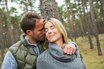 Mid adult couple hugging in forest — Stock Photo