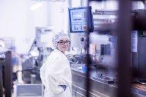 Ouvrier d'usine regardant par-dessus l'épaule à la caméra souriant — Photo de stock