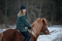 Woman riding horse in snow — Stock Photo
