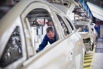 Travailleur, montage d'insonorisation pour voiture en usine automobile — Photo de stock