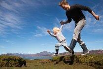 Батько і син тримаючись за руки, біг, острів Скай, Кречом, Марком Ніссеном — стокове фото
