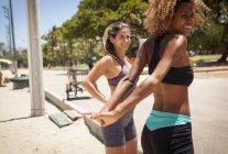 Junge Frauen am Strand dehnen — Stockfoto