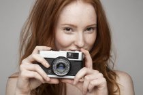 Portrait of young woman, taking photograph — Stock Photo